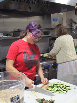 A Cooper chopping vegetables in her houses kitchen.